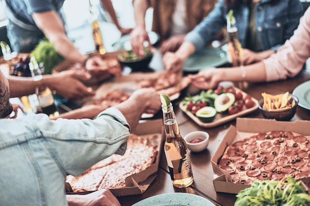 Zo hongerig. close-up van jonge mensen die pizza plukken terwijl ze binnen een etentje hebben