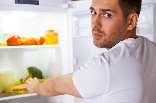 Zo hongerig voelen. verraste jonge man die bij de open koelkast staat en zijn hand uitrekt om een broodje binnen te leggen