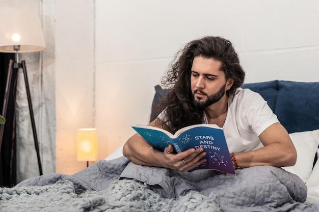 Zo interessant. slimme langharige man zittend op het bed terwijl hij bezig is met lezen