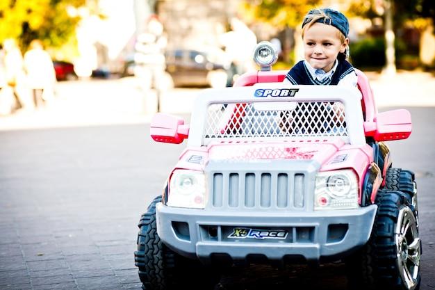 Zo kleine en zo grote jongen. kind ziet er moedig uit om zijn speelgoed buitenland te rijden