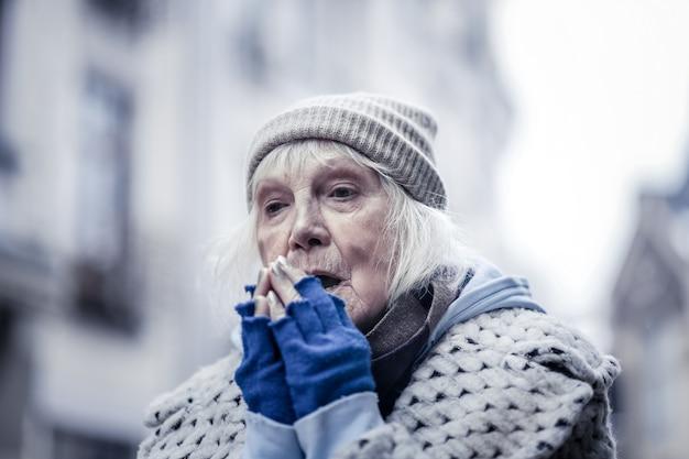 Zo koud. droevige oude vrouw die op straat stond terwijl ze haar handen probeerde te verwarmen