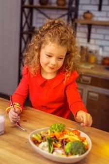 Zo lekker. blij kind dat een glimlach op haar gezicht houdt terwijl ze gezond gaat eten