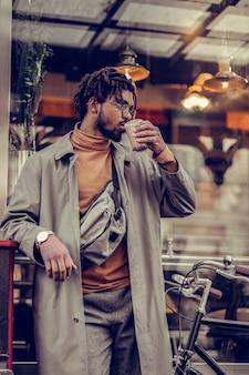 Zo lekker. vrolijke stijlvolle man opzij kijken terwijl het hebben van koffiepauze