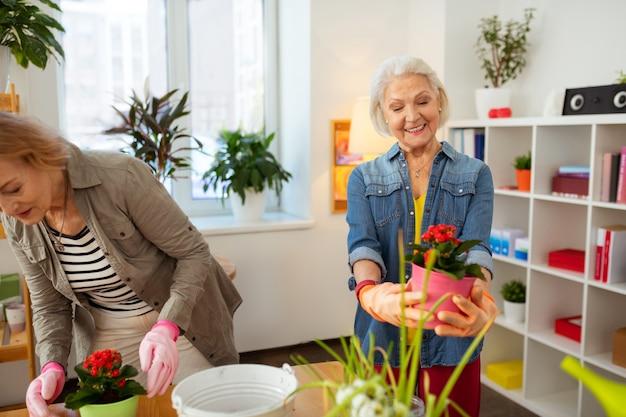 Zo'n mooie bloem. vrolijke oude vrouw die lacht terwijl ze naar de mooie bloem kijkt