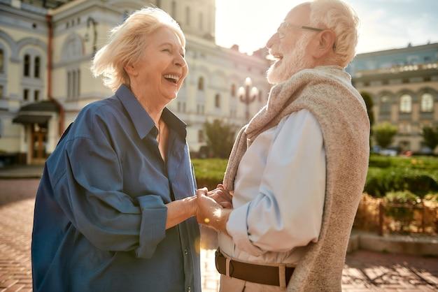 Zo'n prachtige dag gelukkig en mooi bejaarde echtpaar hand in hand en lachend terwijl ze staan