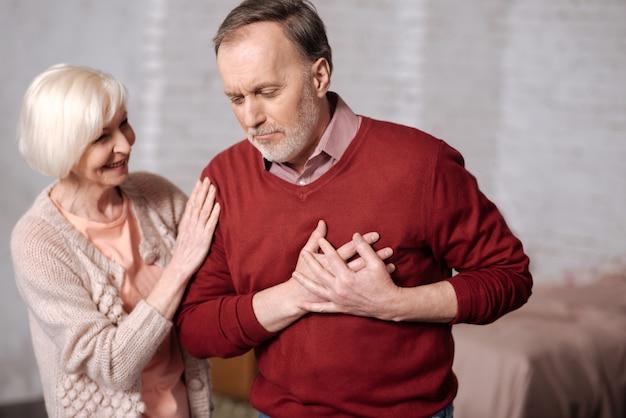 Zo onverwachts. portret van een oude man met hartzeer permanent en zijn hartgebied aan te raken terwijl zijn vrouw hem ondersteunt.