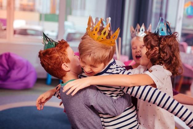 Zo sterk. positieve opgetogen blonde jongen die een glimlach op zijn gezicht houdt en verjaardagsviering heeft