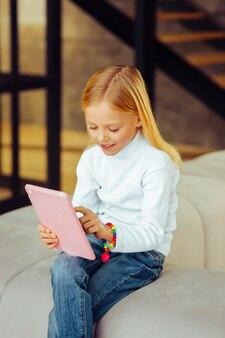 Zo tevreden. attent kind dat positiviteit uitdrukt terwijl het vrije tijd doorbrengt in de woonkamer