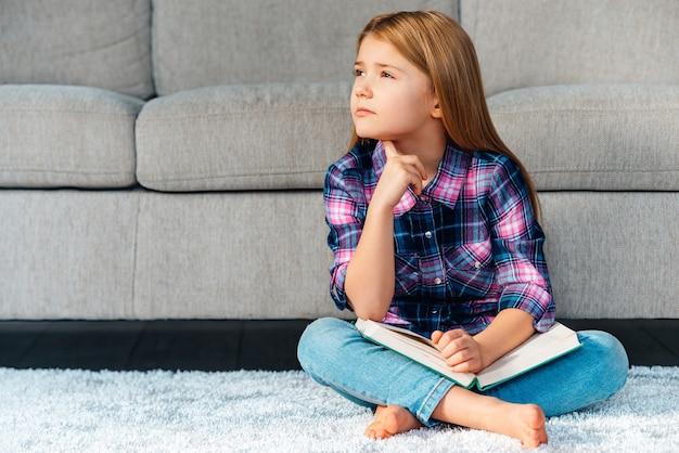 Zo veel vragen. peinzend meisje dat een boek vasthoudt en er attent uitziet terwijl ze thuis op het tapijt in lotushouding zit