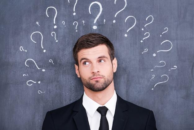 Zo veel vragen! verwarde jonge man die tegen het bord staat met vraagtekens