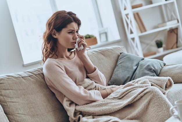 Zo verdrietig voelen. jonge eenzame vrouwen bedekt met een deken huilend terwijl ze thuis op de bank zitten