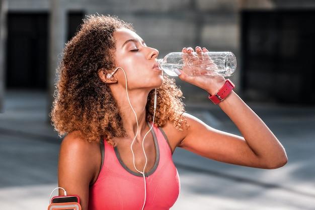 Zo verfrissend. aardige dorstige vrouw die een fles vasthoudt terwijl ze een verse fles drinkt