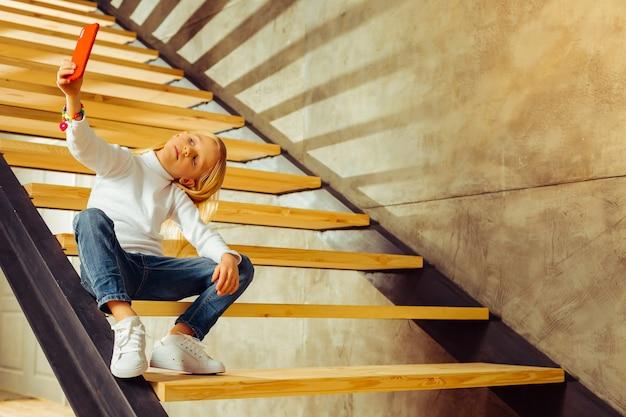 Zo verveeld. blij kind zittend op de trap en kijkend naar haar gadget