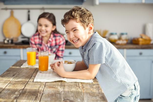 Zo vrolijk. knap opgetogen kleine donkerharige jongen lachen en gezond ontbijten met zijn zus en het meisje lachend in de