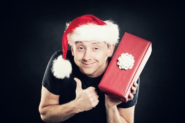 Zoals de kerstman die een duim omhoog en een geschenkdoos toont