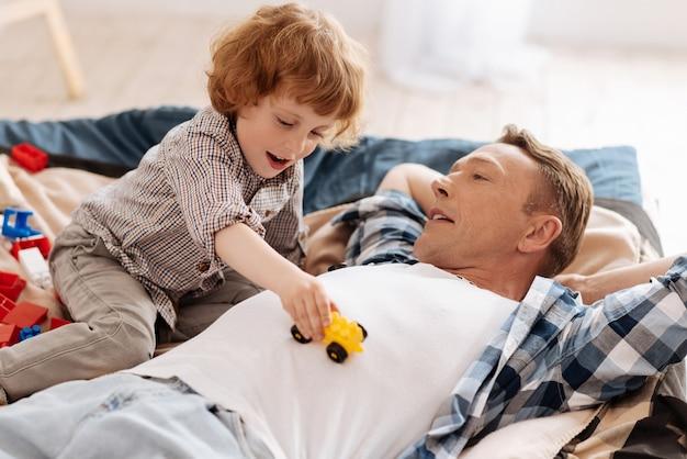 Zoals een massage. opgetogen blonde jongen die zijn mond openhoudt en met speelgoedauto op de buik van zijn vader speelt terwijl hij positiviteit uitdrukt