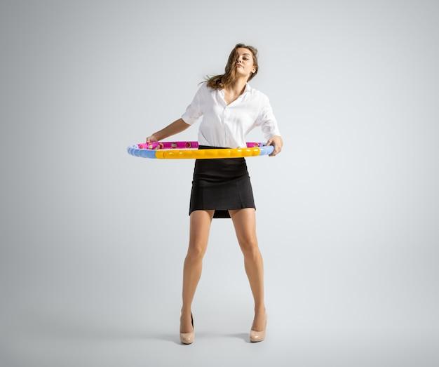 Zoals in de kindertijd. vrouw in kantoorkleding training met hoepel op grijze achtergrond