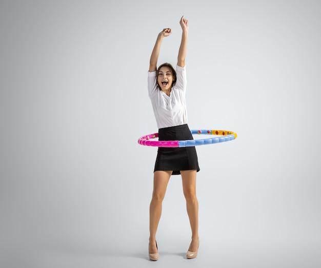 Zoals in de kindertijd. vrouw in kantoorkleding training met hoepel op grijze muur. zakenvrouw training in beweging, actie. ongewone look voor sport, nieuwe activiteit. sporten, gezonde levensstijl.