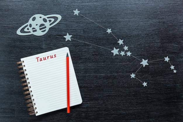 Zodiakale ster, sterrenbeelden stier op een zwarte achtergrond met een notitieblok en potlood.