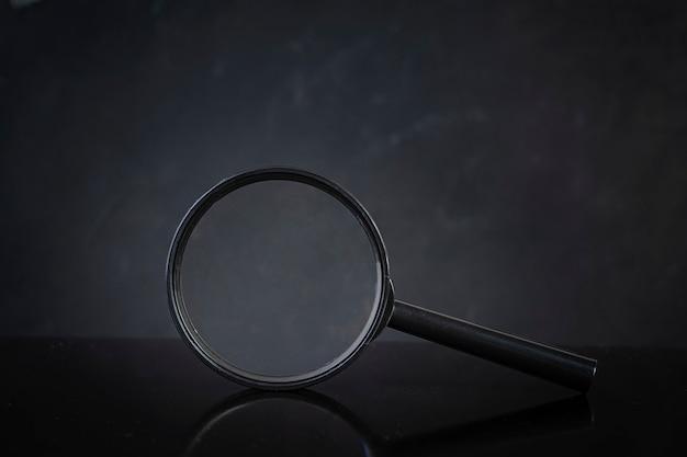 Zoek concept. vergrootglas op donkere achtergrond