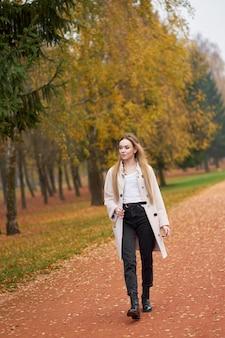 Zoek elke dag. mooie blonde jonge vrouw, gekleed in basic wit overhemd, zwarte moeder jeans, trendy herfstjas en stijlvolle zwarte leren laarzen wandelen in herfst park.