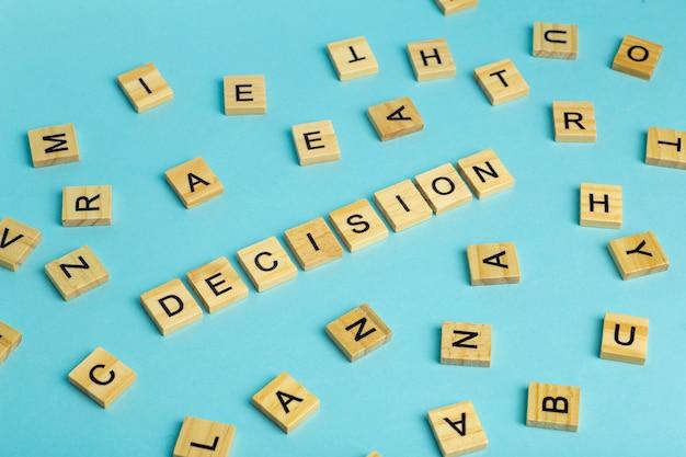 Zoek naar beslissingsconcept. het woord besluit bestaat uit hopen van verschillende letters op een blauwe achtergrond