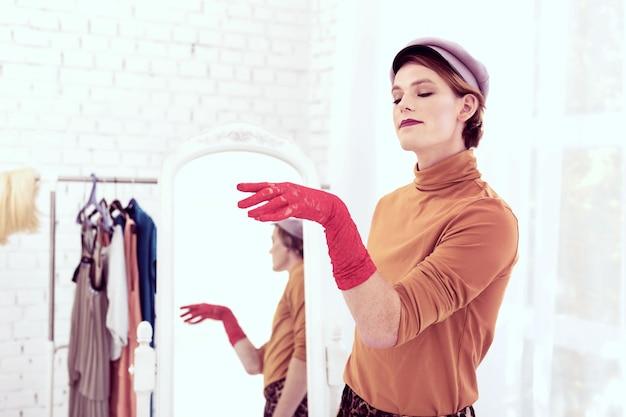Zoek naar nacht. transgender jonge man die blij is met zijn delicate handschoenen terwijl hij aandachtig op zijn hand kijkt