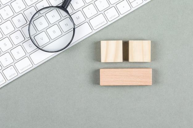 Zoekconcept met meer magnifier, houten blokken, toetsenbord op grijze hoogste mening als achtergrond. horizontaal beeld