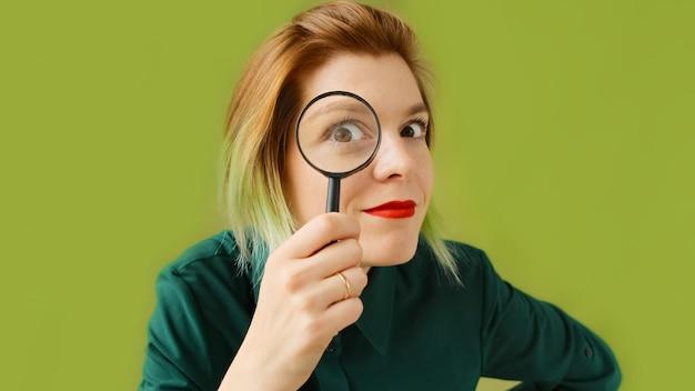 Zoeken. een jonge vrouw met een vergrootglas zoekt, onderzoekt en bestudeert.