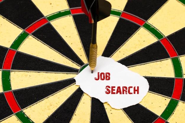 Zoeken naar een baan. darten met dartpijl die op een vel papier was gespeld voor labels