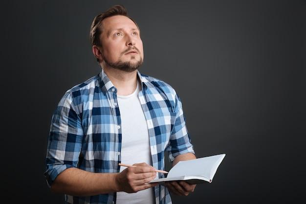 Zoeken naar inspiratie. betoverende jonge bedachtzame man die aan een gedicht werkt en zijn dagboek gebruikt om het op te schrijven