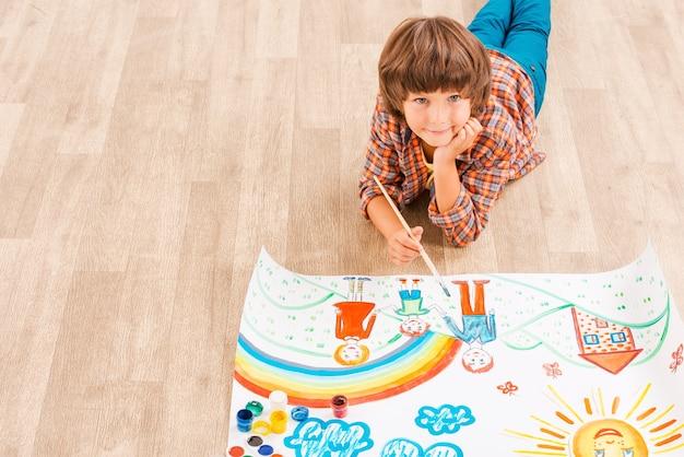 Zoeken naar inspiratie. jonge jongen ontspannen tijdens het schilderen met aquarellen die op de vloer liggen