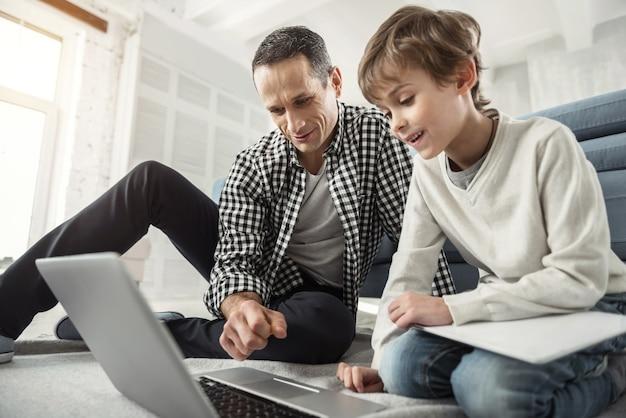 Zoeken op het net. goed uitziende geïnspireerde donkerharige man die lacht en naar de laptop kijkt en zijn zoon die naast hem op de vloer zit