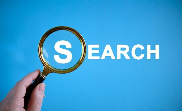 Zoeken - tekst met een vergrootglas op een blauwe achtergrond
