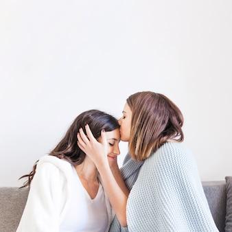 Zoenende liefhebbende vrouwen die thuis knuffelen