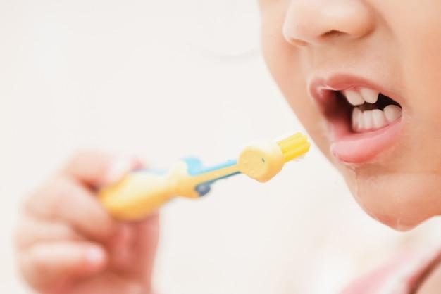 Zoet aziatisch kindmeisje die haar tanden in badkamers borstelen