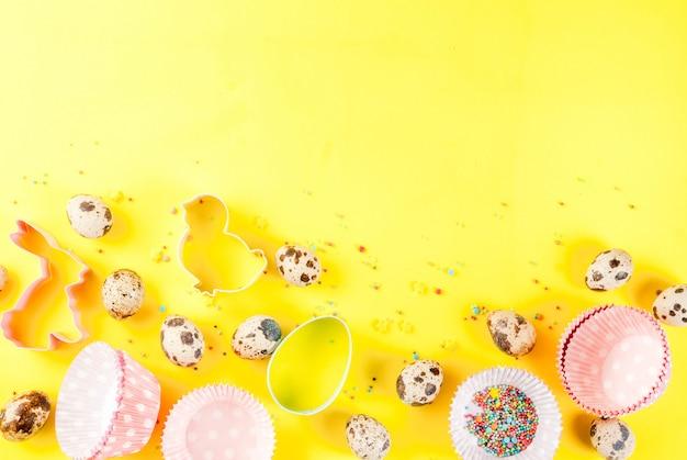 Zoet bakselconcept voor het koken van pasen achtergrond met het bakken - met een deegrol zwaai voor het ranselen van de kwartelseieren van koekjessnijders het bestrooien