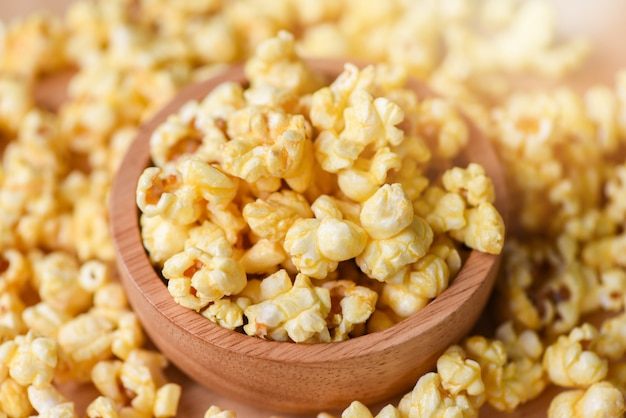 Zoet boterpopcornzout in houten kopkom en pop-up van popcorn backgroubd