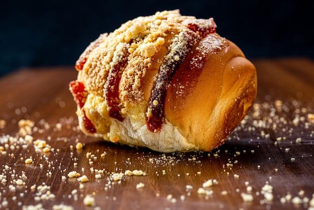 Zoet brood met guave-jam en zoete bloem op een bruine houten tafel. het is een soort brood dat veel voorkomt in brazilië en portugal, gemaakt met zoet deeg.