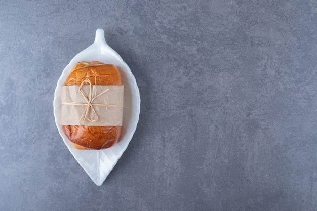 Zoet brood op een schotel op marmeren tafel.