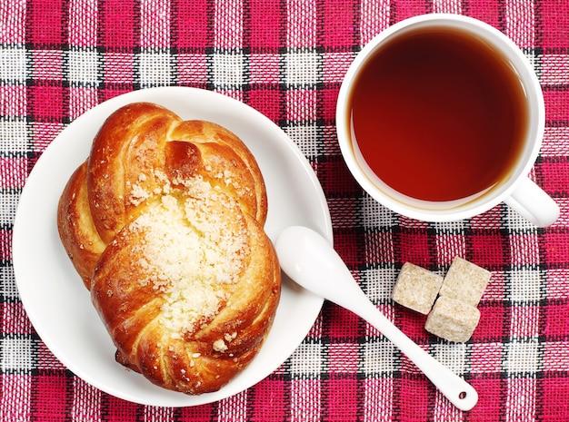Zoet broodje en kopje thee op een rood tafelkleed. bovenaanzicht