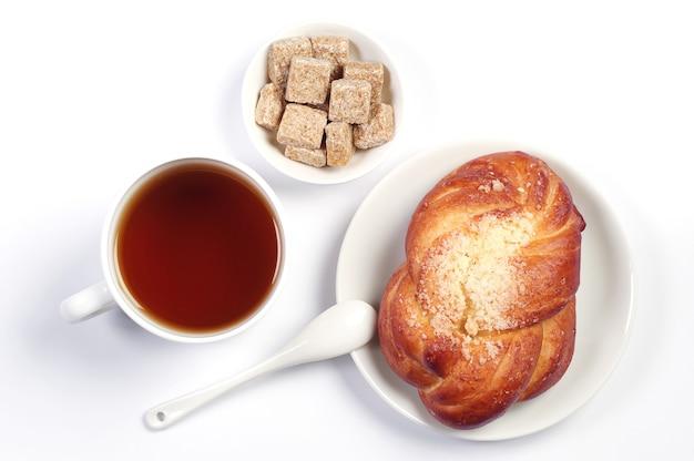 Zoet broodje en kopje thee op witte achtergrond. bovenaanzicht