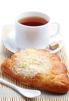 Zoet broodje en kopje thee op witte tafel