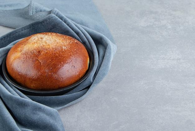 Zoet broodje met doek op stenen tafel.
