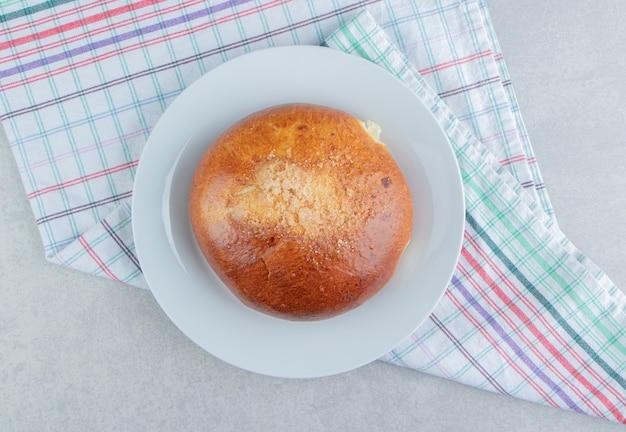 Zoet broodje met doek op witte plaat.