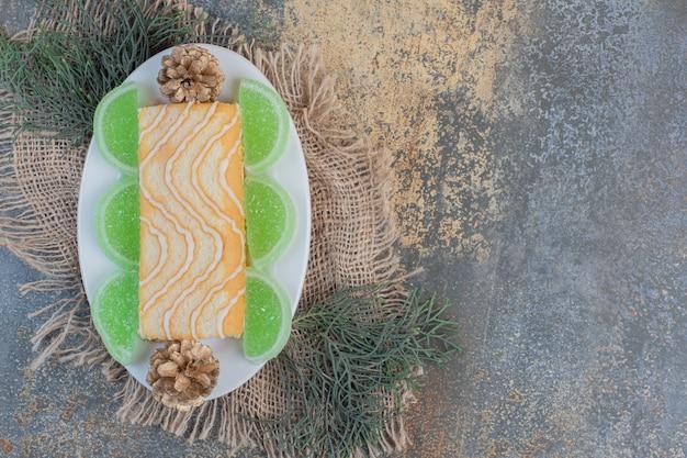 Zoet broodje met groene marmelades en dennenappels op een witte plaat. hoge kwaliteit foto