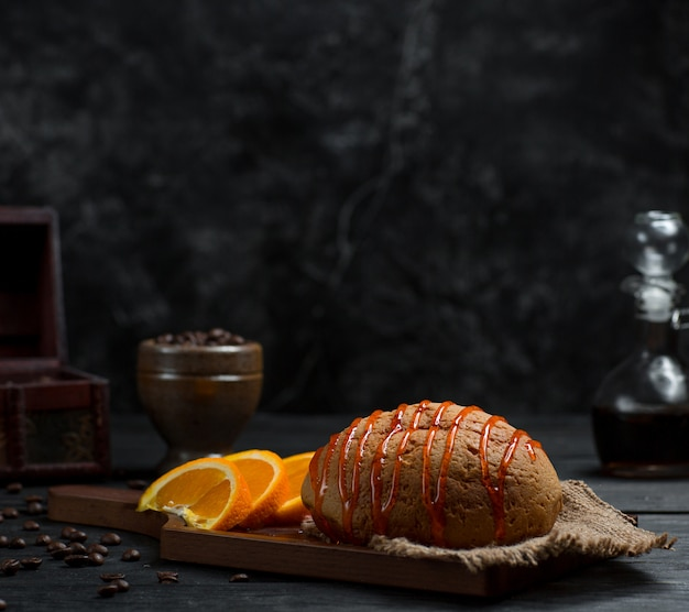 Zoet broodje met kersensiroop en gesneden oranje fruit