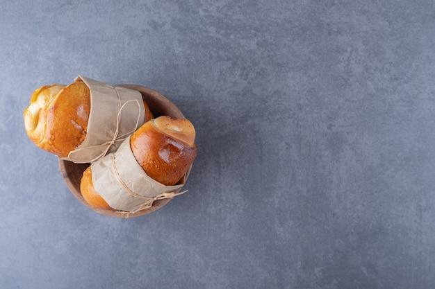 Zoet broodje vastgebonden met een draad in een kom op marmeren tafel.