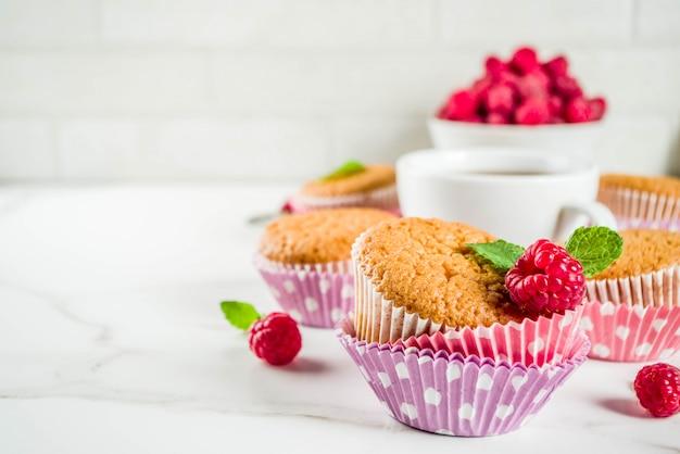 Zoet dessert, zelfgemaakte gebakken muffin met frambozenjam, geserveerd met thee, verse frambozen en munt
