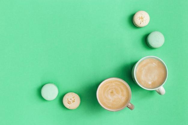 Zoet eten, smakelijke bitterkoekjes en warme geurige koffie met melkschuim. twee kop cappuccino en heerlijk dessert op de muntachtergrond van de tendenskleur.